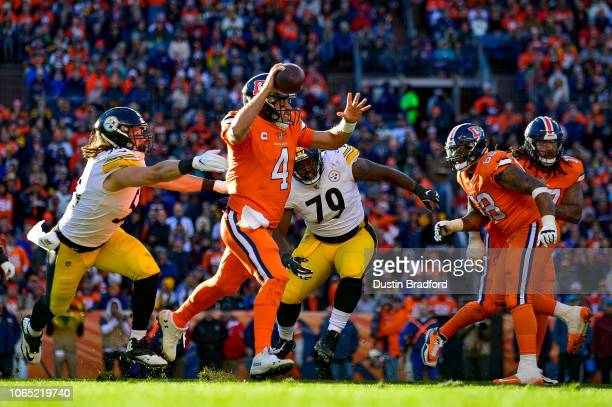Quarterback Case Keenum of the Denver Broncos scrambles out of the pocket under pressure by nose tackle Javon Hargrave and linebacker Anthony...