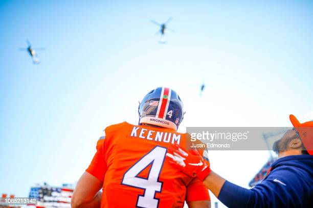 Quarterback Case Keenum of the Denver Broncos stands on the field as armed forces helicopters perform a flyover during the performance of the...