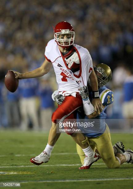 Quarterback Case Keenum of the Houston Cougars is tied up by linebacker Sean Westgate of the UCLA Bruins at the Rose Bowl on September 18 2010 in...
