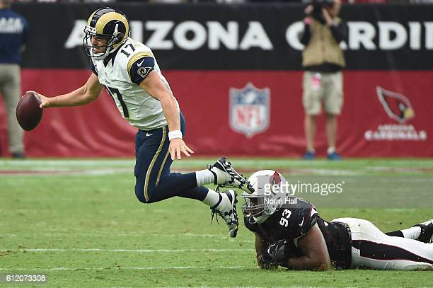Quarterback Case Keenum of the Los Angeles Rams scrambles to make a pass against defensive end Calais Campbell of the Arizona Cardinals during the...