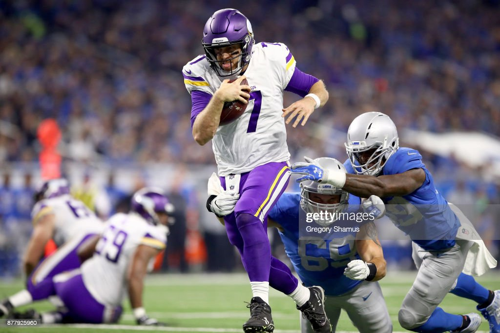 Quarterback Case Keenum #7 of the Minnesota Vikings runs with the ball against Anthony Zettel #69 of the Detroit Lions and Tahir Whitehead #59 for a touchdown against the Detroit Lions during the first half at Ford Field on November 23, 2017 in Detroit, Michigan.