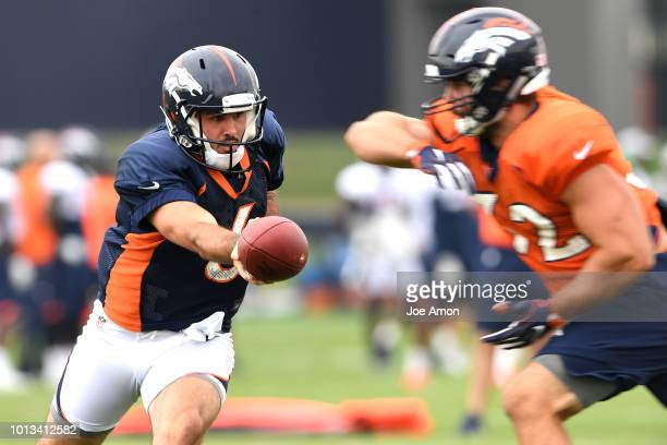Quarterback Chad Kelly hands off to fullback Andy Janovich during Denver Broncos training camp at the UCHealth Training Center August 8 2018 in...