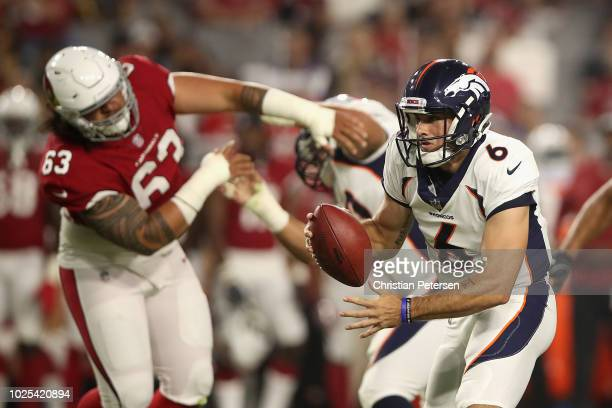 Quarterback Chad Kelly of the Denver Broncos looks to pass under pressure from defensive tackle Peli Anau of the Arizona Cardinals during the...