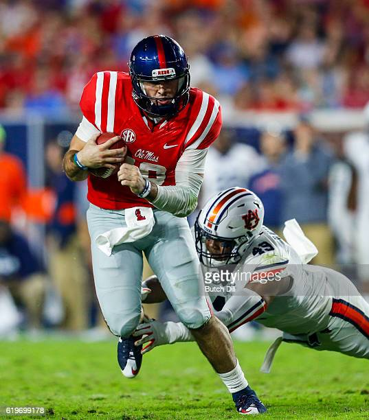 Quarterback Chad Kelly of the Mississippi Rebels scrambles for yardage as linebacker Darrell Williams of the Auburn Tigers dives for the tackle...