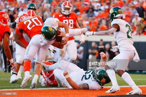 Quarterback Charlie Brewer of the Baylor University Bears spins airborne and shoeless into the end zone for a touchdown against the Oklahoma State...