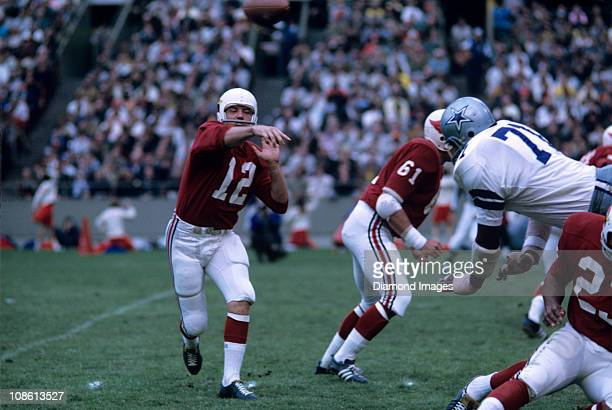 Quarterback Charlie Johnson of the St Louis Cardinals throws a pass as defensive end Willie Townes of the Dallas Cowboys dives over the offensive...