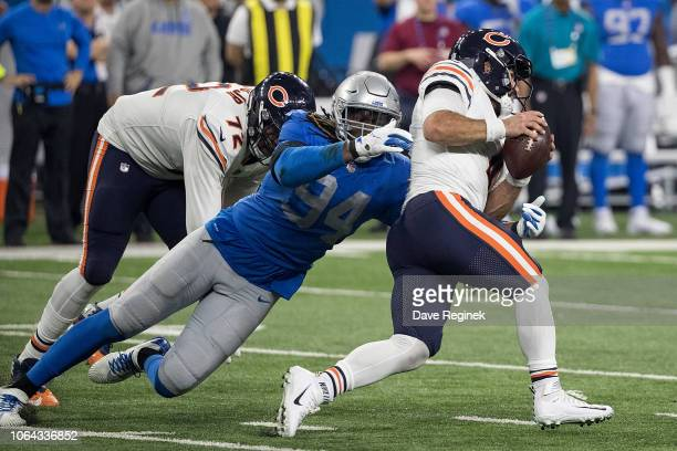 Quarterback Chase Daniel of the Chicago Bears runs with the ball while being wrapped up by Ezekiel Ansah of the Detroit Lions during an NFL game at...