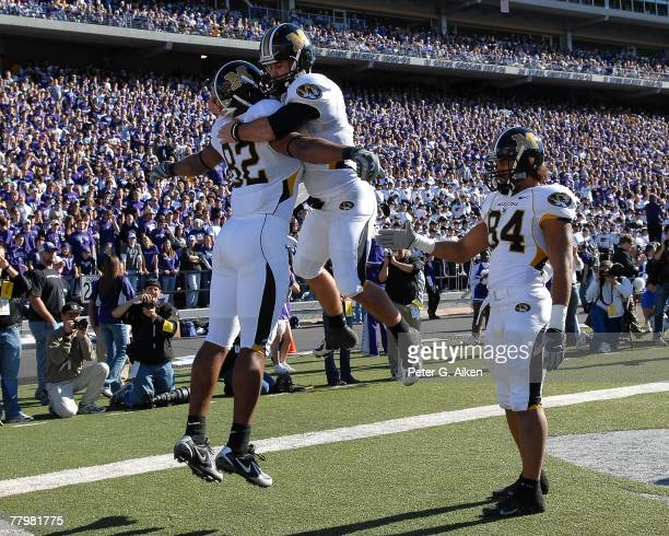 Quarterback Chase Daniel of the Missouri Tigers jumps into tight end Martin Rucker's arms as teammate Tommy Saunders looks on after scoring on a...