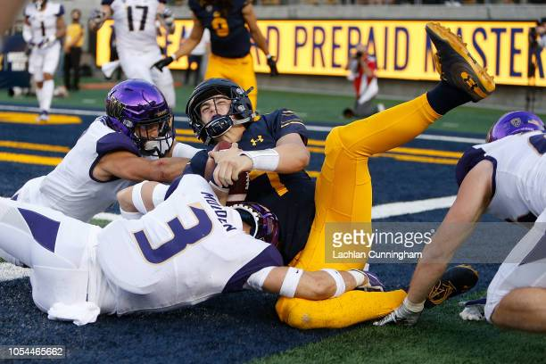 Quarterback Chase Garbers of the California Golden Bears is tackled out of bounds by Elijah Molden and Taylor Rapp of the Washington Huskies at...