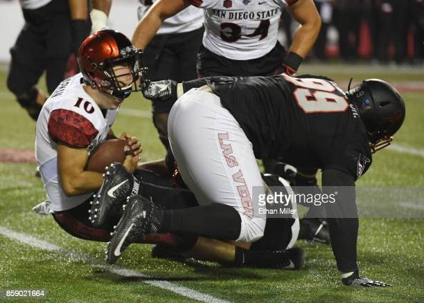 Quarterback Christian Chapman of the San Diego State Aztecs is sacked by defensive linemen Mike Hughes Jr #99 and Roger Mann of the UNLV Rebels...