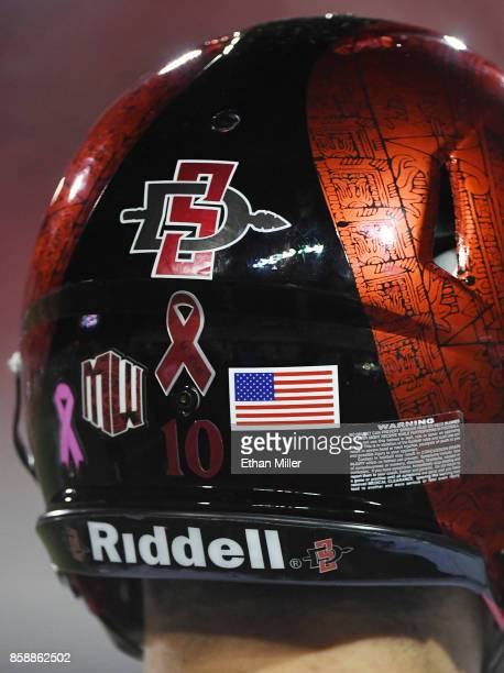 Quarterback Christian Chapman of the San Diego State Aztecs wears a helmet with a red ribbon on it in honor of the victims of Sunday's mass shooting...