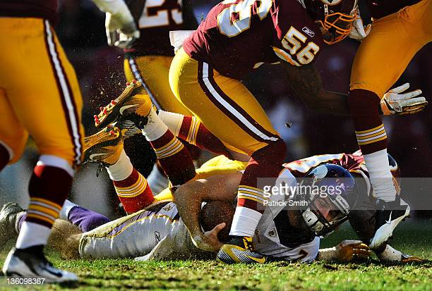 Quarterback Christian Ponder of the Minnesota Vikings takes a hit from from Washington Redskins defenders in the first quarter at FedEx Field on...