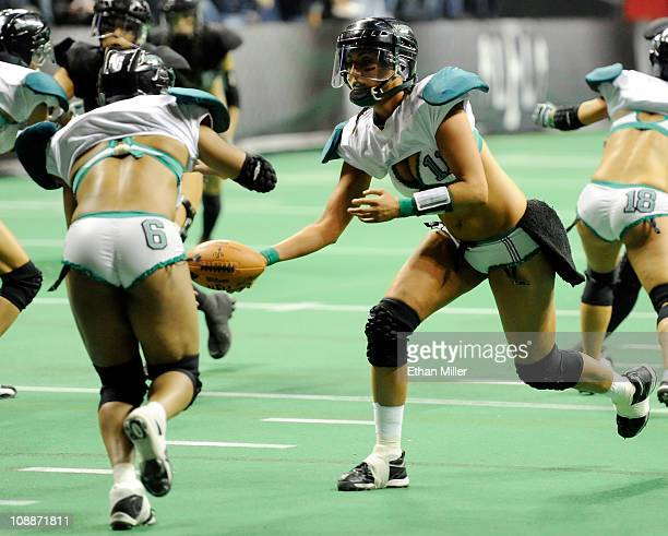 Quarterback Christy Bell of the Philadelphia Passion hands the ball off to Marirose Roach as they take on the Los Angeles Temptation during the...