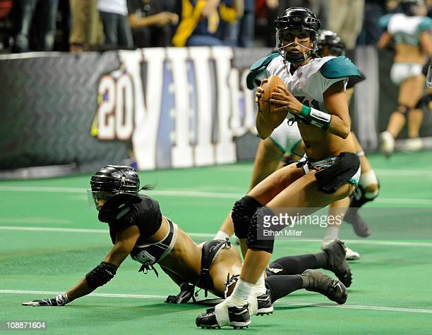 Quarterback Christy Bell of the Philadelphia Passion scrambles after avoiding a tackle by Zipphora Chase of the Los Angeles Temptation during the...