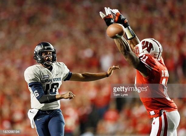 Quarterback Chuckie Keeton of the Utah State Aggies passes the ball past defensive end David Gilbert of the Wisconsin Badgers during the second...