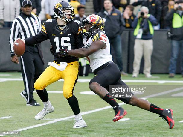 Quarterback CJ Beathard of the Iowa Hawkeyes looks to get rid of the ball under pressure from defensive lineman Yannick Ngakoue of Maryland Terrapins...