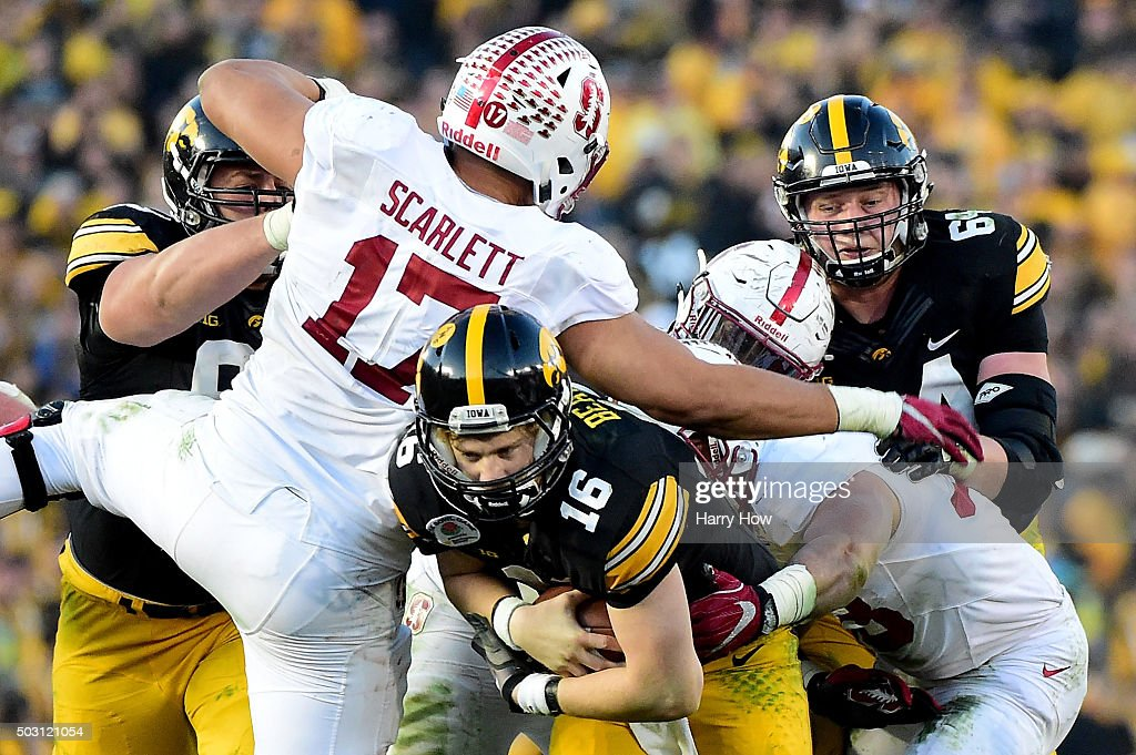 Quarterback C.J. Beathard #16 of the Iowa Hawkeyes tries to move past Brennan Scarlett #17 and Mike Tyler #33 of the Stanford Cardinal in the 102nd Rose Bowl Game on January 1, 2016 at the Rose Bowl in Pasadena, California.