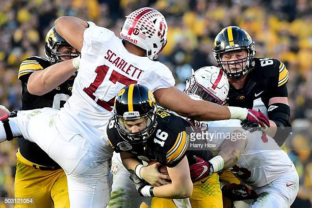 Quarterback CJ Beathard of the Iowa Hawkeyes tries to move past Brennan Scarlett and Mike Tyler of the Stanford Cardinal in the 102nd Rose Bowl Game...