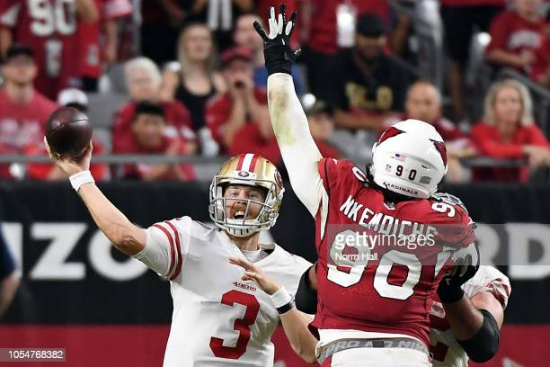 Quarterback CJ Beathard of the San Francisco 49ers throws under pressure from defensive tackle Robert Nkemdiche of the Arizona Cardinals during the...