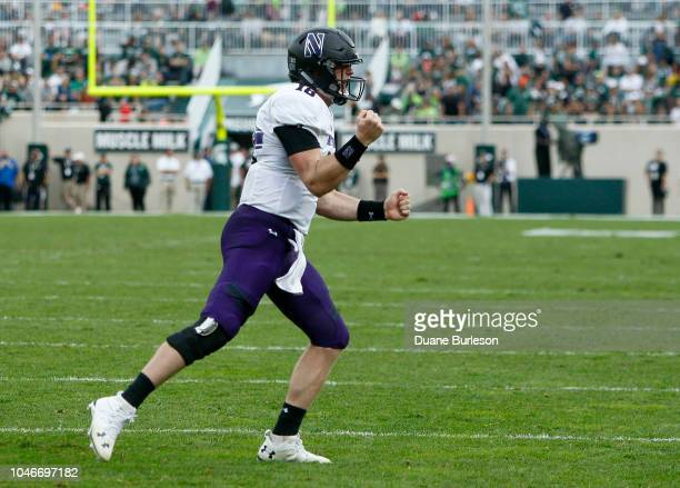 Quarterback Clayton Thorson of the Northwestern Wildcats celebrates after scoring against the Michigan State Spartans during the fourth quarter at...