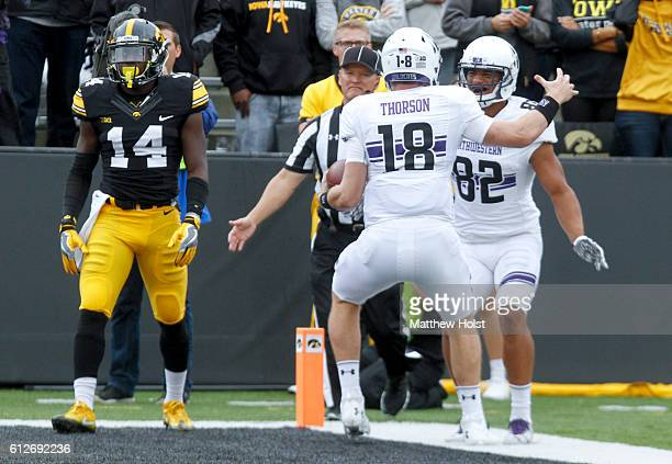 Quarterback Clayton Thorson of the Northwestern Wildcats celebrates with wide receiver Andrew Scanlan after a touchdown in the first quarter against...