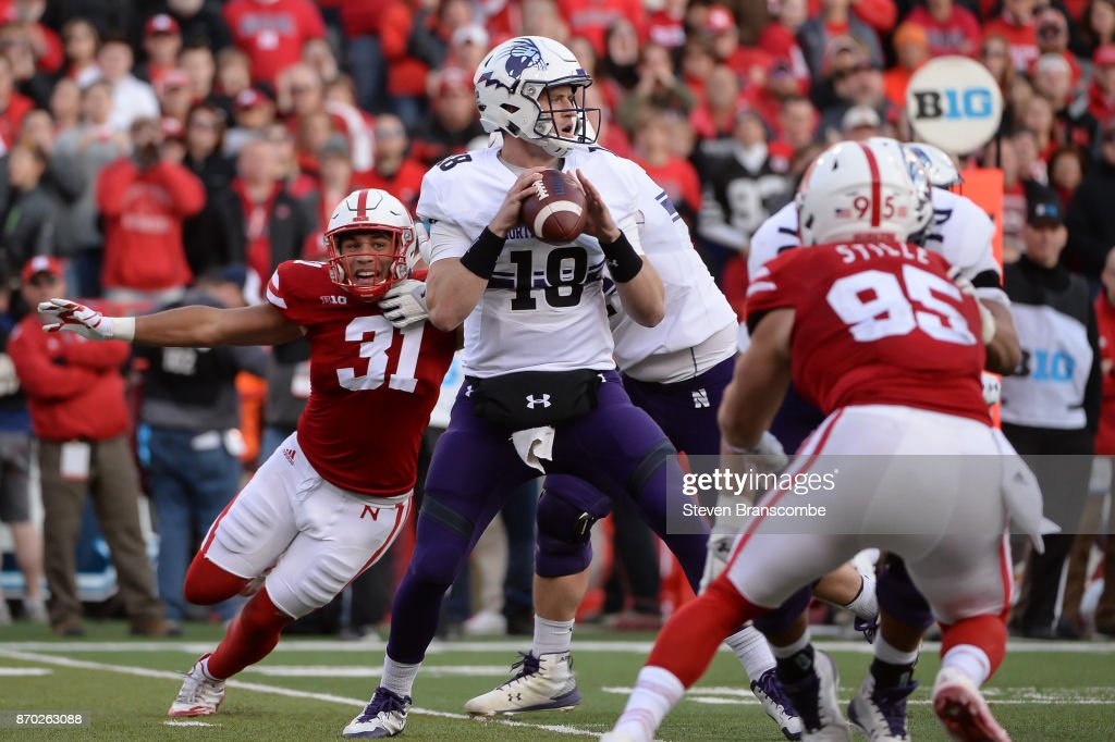 Quarterback Clayton Thorson #18 of the Northwestern Wildcats passes ahead of the rush from linebacker Collin Miller #31 of the Nebraska Cornhuskers at Memorial Stadium on November 4, 2017 in Lincoln, Nebraska.
