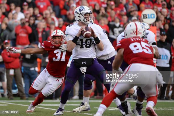 Quarterback Clayton Thorson of the Northwestern Wildcats passes ahead of the rush from linebacker Collin Miller of the Nebraska Cornhuskers at...