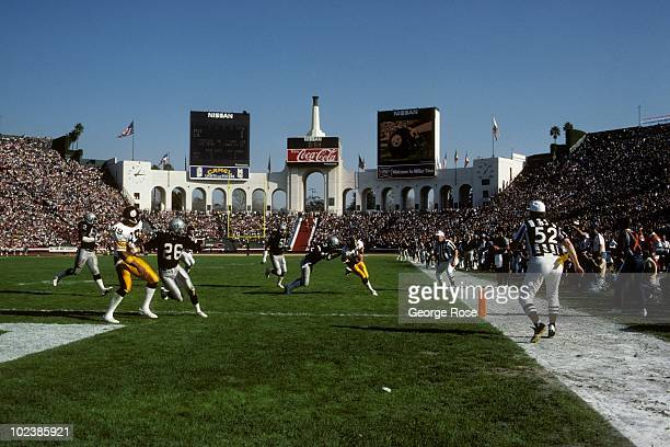 Quarterback Cliff Stoudt of the Pittsburgh Steelers runs to the end zone against Los Angeles Raiders linebacker Rod Martin during the 1983 AFC...