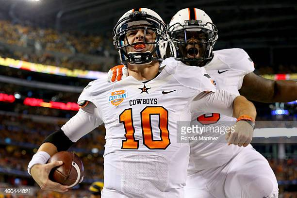 Quarterback Clint Chelf of the Oklahoma State Cowboys celebrates with Kye Staley after Chelf rushes for a 23-yard touchdown in the fourth quarter...