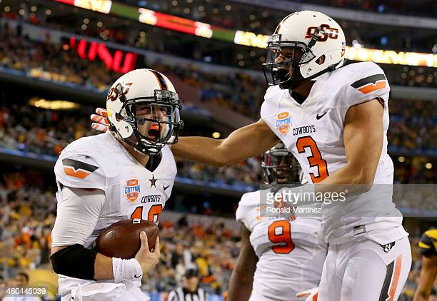 Quarterback Clint Chelf of the Oklahoma State Cowboys celebrates with Marcell Ateman after Chelf rushes for a 23-yard touchdown in the fourth quarter...