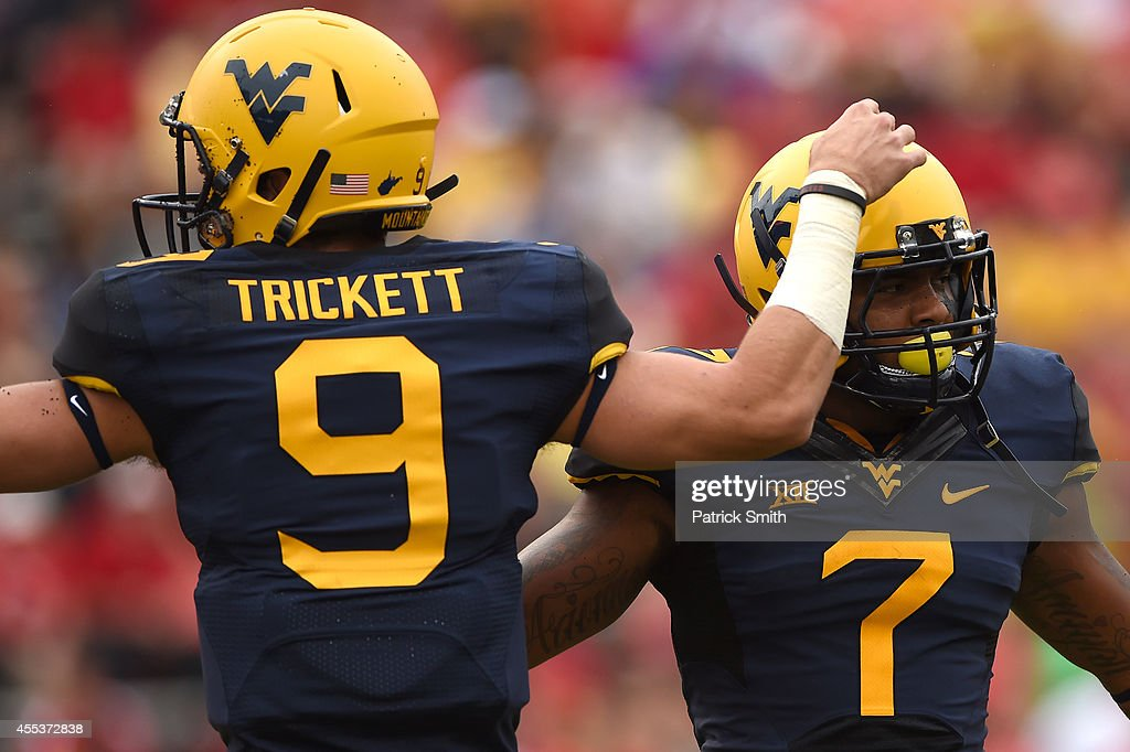Quarterback Clint Trickett #9 of the West Virginia Mountaineers celebrates running back Rushel Shell #7 first quarter touchdown against the Maryland Terrapins during an NCAA college football game at Capital One Field at Byrd Stadium on September 13, 2014 in College Park, Maryland.