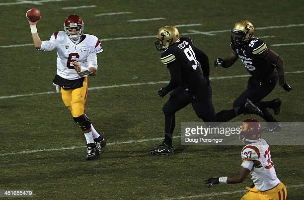 Quarterback Cody Kessler of the USC Trojans eludes defensive lineman Kirk Poston of the Colorado Buffaloes and defensive lineman Chidera UzoDiribe of...