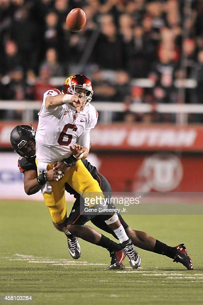 Quarterback Cody Kessler of the USC Trojans passes while being tackled by end Nate Orchard of the Utah Utes at Rice-Eccles Stadium on October 25,...