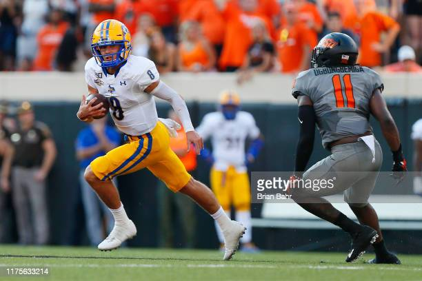 Quarterback Cody Orgeron of the McNeese State Cowboys runs to the outside to escape linebacker Amen Ogbongbemiga of the Oklahoma State Cowboys in the...