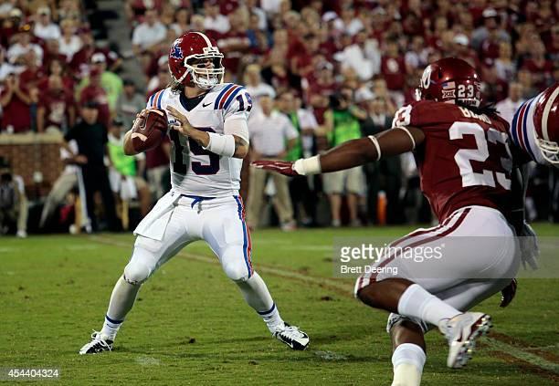 Quarterback Cody Sokol of the Louisiana Tech Bulldogs looks to throw under pressure from linebacker Devante Bond of the Oklahoma Sooners August 30,...
