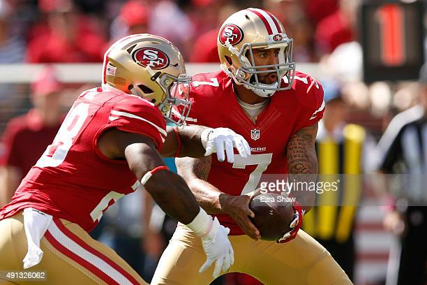 Quarterback Colin Kaepernick looks to hand the ball off to running back Carlos Hyde of the San Francisco 49ers during their NFL game against the...