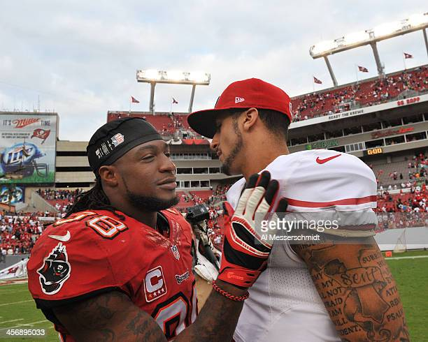 Quarterback Colin Kaepernick of the San Francisco 49ers greets safety Dashon Goldson of the Tampa Bay Buccaneers after the game December 15 2013 at...