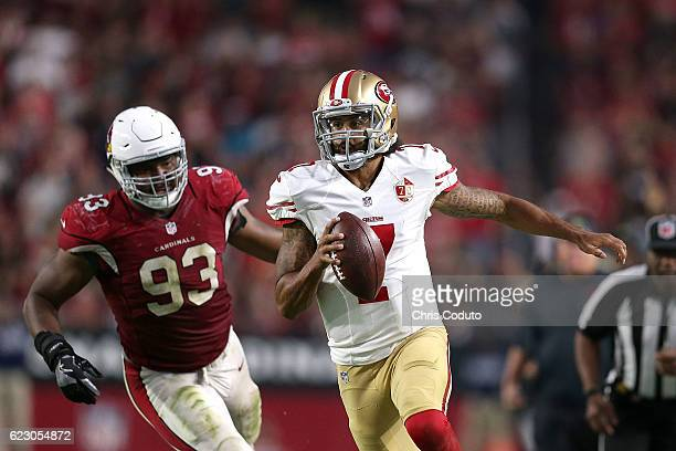 Quarterback Colin Kaepernick of the San Francisco 49ers runs past defensive end Calais Campbell of the Arizona Cardinals during the fourth quarter of...