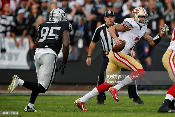 Quarterback Colin Kaepernick of the San Francisco 49ers scrambles while looking for a receiver against defensive end Benson Mayowa of the Oakland...