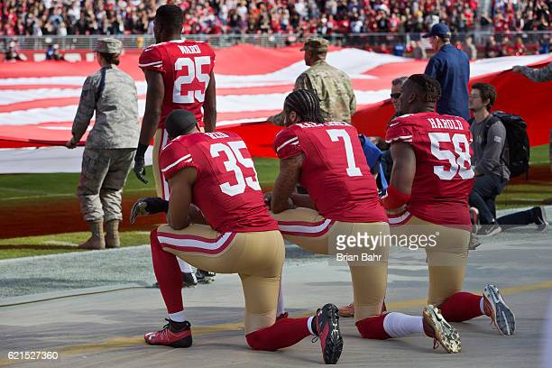 Quarterback Colin Kaepernick safety Eric Reid and linebacker Eli Harold of the San Francisco 49ers kneel before a game against the New Orleans Saints...