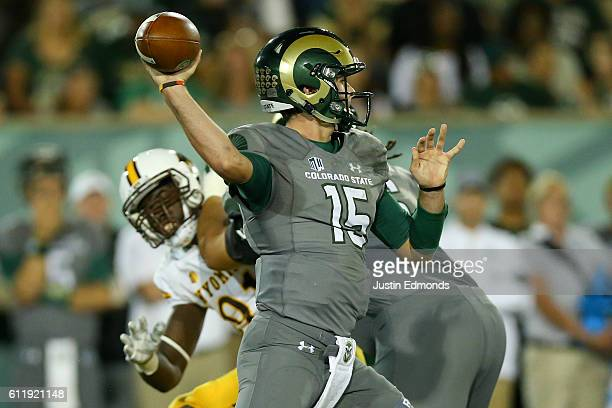 Quarterback Collin Hill of the Colorado State Rams throws a pass under pressure from the Wyoming Cowboys at Sonny Lubick Field at Hughes Stadium on...