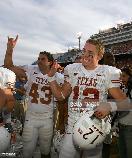 Quarterback Colt McCoy and punt kicker Justin Moore of the Texas Longhorns raise the Hold 'em Horns sign after winning the game against the Oklahoma...