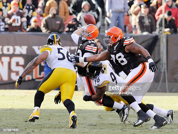 Quarterback Colt McCoy of the Cleveland Browns is tackled while passing by defensive lineman Ziggy Hood of the Pittsburgh Steelers as offensive...