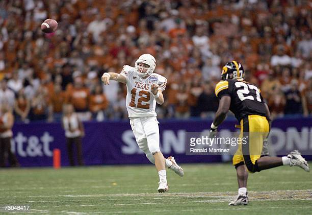 Quarterback Colt McCoy of the Texas Longhorns passes the ball against Ed Miles of the Iowa Hawkeyes during the Alamo Bowl on December 30 2006 at the...