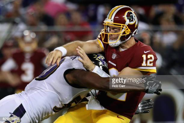 Quarterback Colt McCoy of the Washington Redskins gets off a pass while being hit by outside linebacker Albert McClellan of the Baltimore Ravens in...