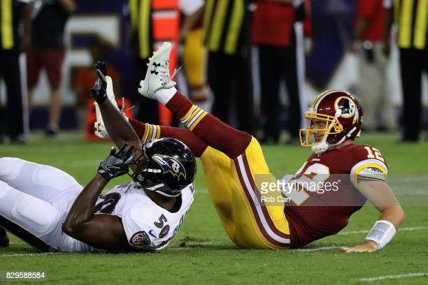 Quarterback Colt McCoy of the Washington Redskins is hit by outside linebacker Albert McClellan of the Baltimore Ravens after throwing a first half...