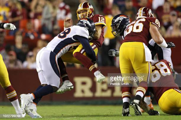 Quarterback Colt McCoy of the Washington Redskins takes a hit after releasing a pass by linebacker Von Miller of the Denver Broncos in the first half...