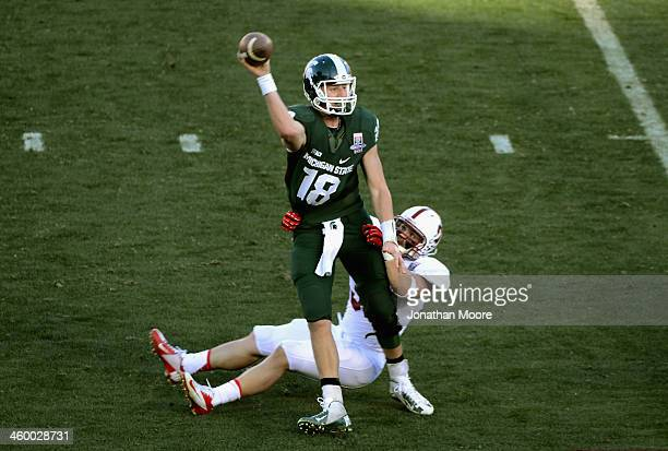 Quarterback Connor Cook of the Michigan State Spartans his hit as he throws during the 100th Rose Bowl Game presented by Vizio against the Stanford...