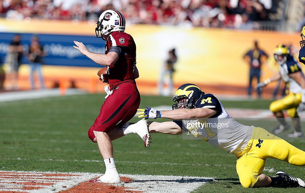Quarterback Connor Shaw #14 of the South Carolina Gamecocks runs away from defender Brennen Beyer #97 of the Michigan Wolverines during the Outback Bowl Game at Raymond James Stadium on January 1, 2013 in Tampa, Florida.