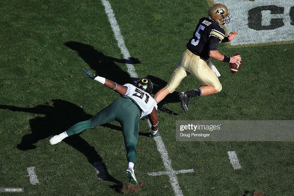 Quarterback Connor Wood #5 of the Colorado Buffaloes scrambles to elude defensive end Tony Washington #91 of the Oregon Ducks at Folsom Field on October 5, 2013 in Boulder, Colorado. The Ducks defeated the Buffs 57-16.